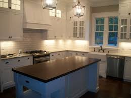 shade of white subway tile backsplash with white cabinets