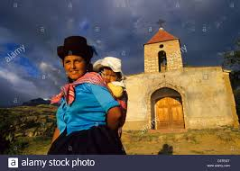 young smiling indian mother with baby on her back in front of a