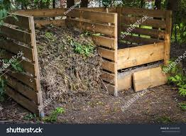 wooden compost boxes with composted soil and yard waste for garden