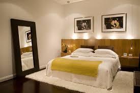 bedroom custom headboard with dark wood floors and floor mirror