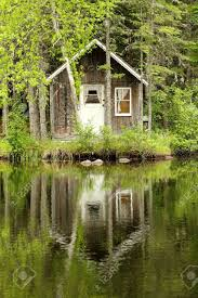 little wood house making a reflection on a calm lake stock photo
