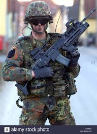 a soldier equipped with hi tech weapon prototype is aiming at a