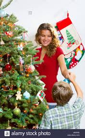 sister and brother decorating a noble fir christmas tree with