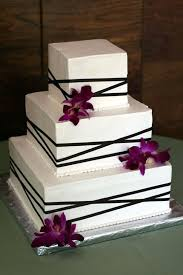 a square wedding cake wrapped in brown ribbon with fresh purple