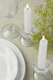 plates that stick to table white vintage empty plates wine glass lit stick candles yellow