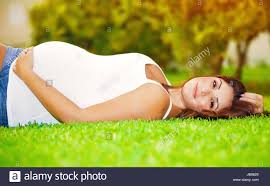 cute pregnant woman lying down on fresh green grass on the