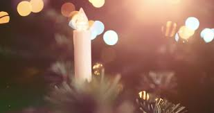slow twinkling christmas lights blinking electric candle in front of abstract blurred christmas