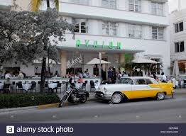 classic car and motorbike in front of art deco hotel avalon on