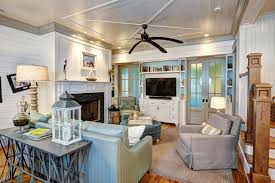 coastal living room with fireplace large ceiling fan tv and