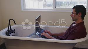 laptop bathtub stock video man on laptop in empty bath tub 35290364
