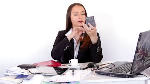 business woman applying makeup while siting at her working office