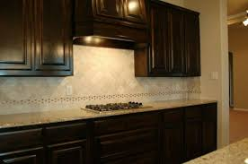 Dark Brown Cabinets Installed In The Kitchen With Tumbled Marble - Marble backsplashes