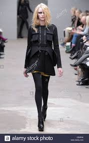 black textured dress with chest pockets gold shorts black tights