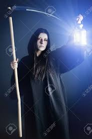 background halloween image woman death reaper over black background halloween stock photo