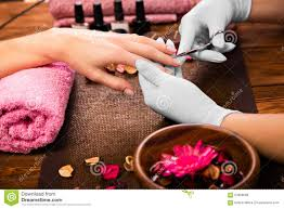 closeup finger nail care by manicure specialist in beauty salon