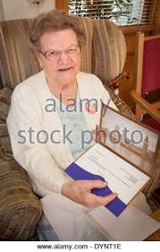 elderly woman with her 100th birthday card from the queen and