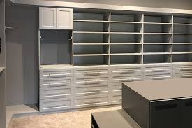 walk in closet with drawers center island and pull down closet rods