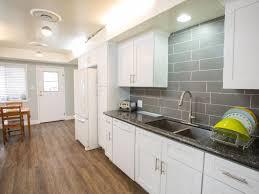 new white kitchen cabinets with gray quartz countertops which are