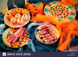 some plates with halloween food such as candies scary fingers or