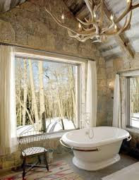 rustic bathroom style with large awning window and stone wall and