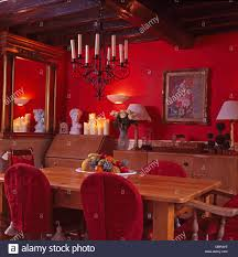 Red Chandelier by Wrought Iron Candle Chandelier Above Simple Wood Table And Chairs