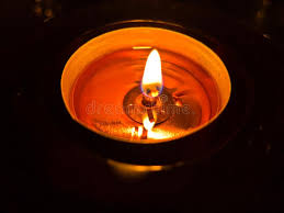 light up christmas candles light of one small christmas candle in a dark room stock photo