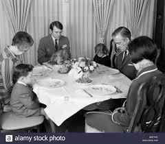 1960s three generation family saying grace prayer at thanksgiving