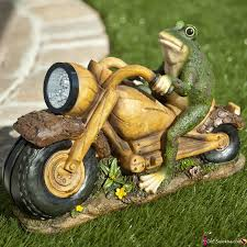 solar light frog on motorcycle statue amongst the flowers