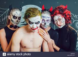background pattern halloween three girls and a guy with halloween face art on dark background