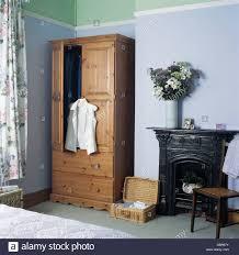 black cast iron edwardian fireplace in pale blue bedroom with black cast iron edwardian fireplace in pale blue bedroom with white shirt hanging on new pine wardrobe
