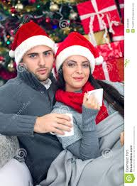 young and smiling couple with santa hat relaxing in x mas night