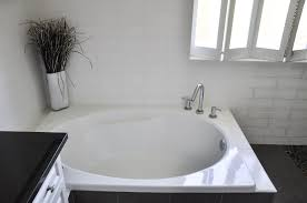 exquisite small bathroom design with white bathtub along wood