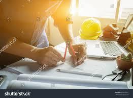 architect working on blueprintengineer inspective workplace stock