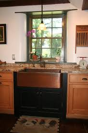 apron copper kitchen sink installed with granite countertops and