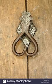 heart shaped metal door knocker of a wooden front door stock photo
