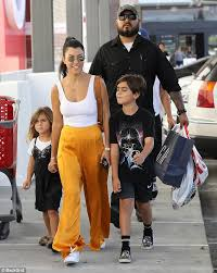 kourtney kardashian wears yellow pants while with her kids