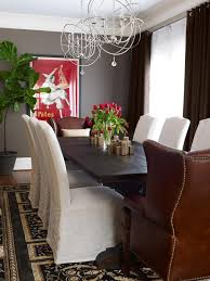 photo page hgtv bright transitional dining room with gray walls slipcover chairs brown leather head chairs and deep wood dining table