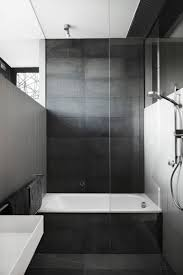 large dark tiles cover the floor bath surround and back wall of this bathroom creating a dark dramatic look but when paired with white walls it creates