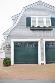 pretty yellow house with dark green carriage style doors and an