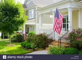 Porch Flag An American Flag Hangs From A Front Porch In A Neighborhood Of