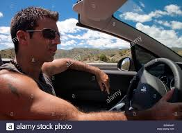 Cool Stock by Cool Guy Driving A Convertible Car Through A Desert Stock Photo