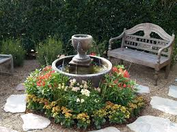 simple front yard fountain with beautiful red and yellow flowers