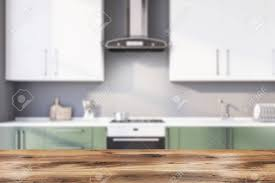 white kitchen cabinets with green countertops table for your product in blurry kitchen with gray walls green