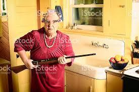 kitchen gun grumpy granny in kitchen with gun stock photo 471777273 istock