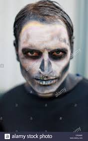 man made up with face paint to look like a skeleton haloween stock