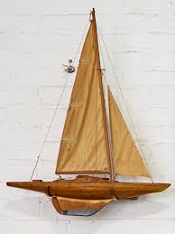 vintage wooden sailboat with custom brass wall mount in the