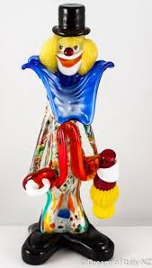 the murano glass clown stands holding a traditional italian