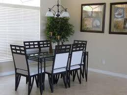 rectangular glass top dining table with black iron pedestal of