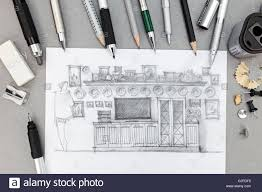 designer workplace with freehand sketch of wall unit and drawing