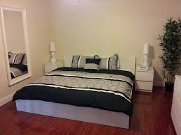 bedroom grey platform bed white nightstands white desk lamps